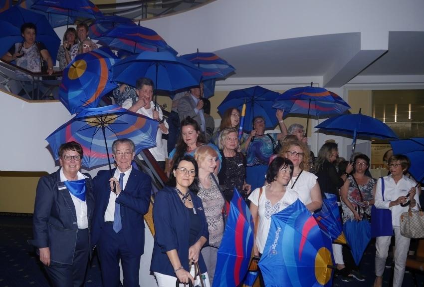 Das Bild zeigt Teilnehmer der SHG Weiterbildung beim Gruppenbild mit Schirm.